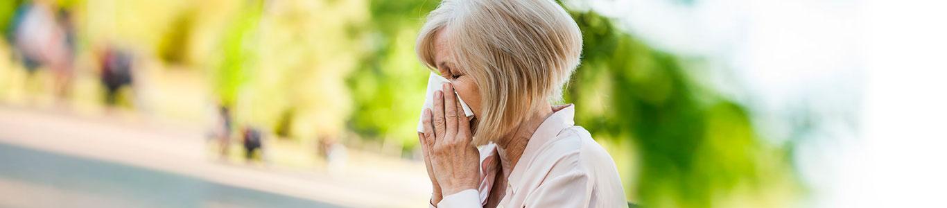 Mujer adulto mayor sonándose en exterior temporada verano de influenza