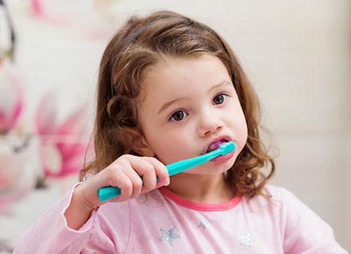 Niña pequeña lavándose los dientes