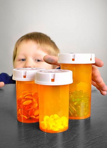 Niño tratando de tomar unas cajas de pastillas