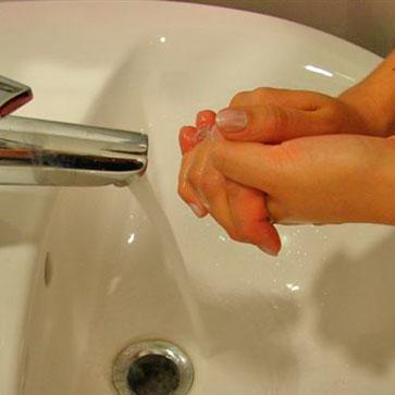 manos frotándose jabón con agua